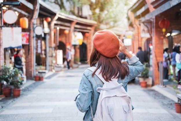 Reisende der jungen frau, die in der einkaufsstraße, reiselebensstilkonzept geht