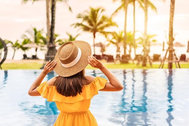 Reisende der jungen frau, die sich entspannt und den sonnenuntergang durch einen tropischen resortpool genießt, während sie für sommerferien reist
