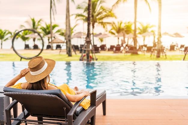 Reisende der jungen frau, die sich entspannt und den sonnenuntergang durch einen tropischen resortpool während der reise genießt
