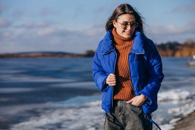 Reisende der jungen frau in der blauen jacke auf dem strand
