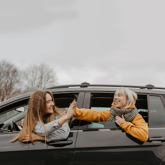 Reisende, die aus autofenster heraus feiern