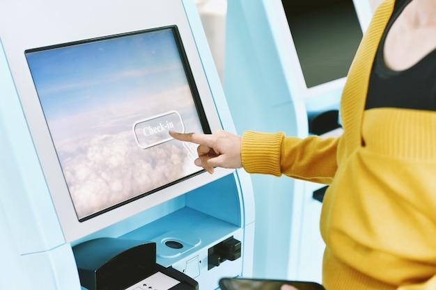 Reisende, die einen self-check-in-automaten am flughafen nutzen