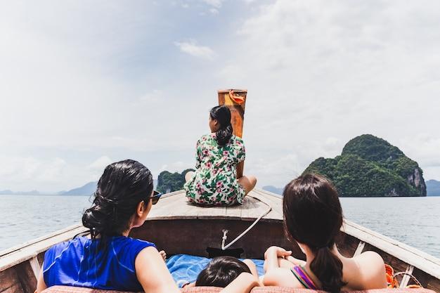 Reisende familie sitzen auf long tail boot im urlaub.