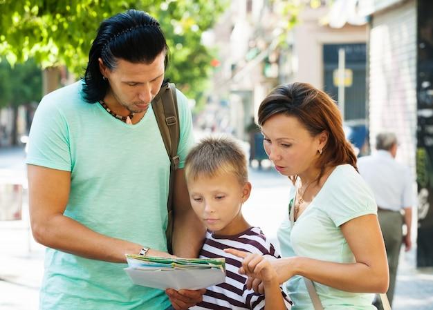 Reisende familie, welche die karte betrachtet