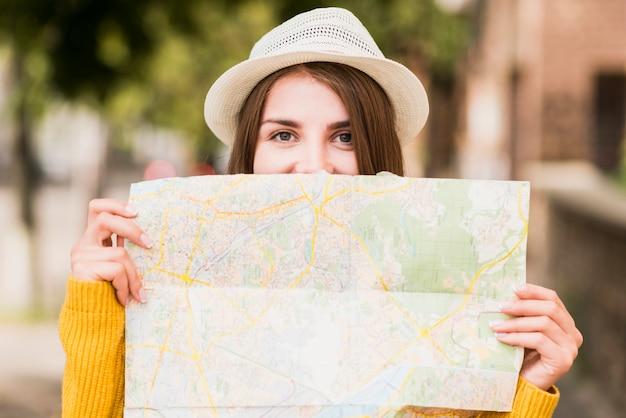 Reisende frau des smiley, die karte hält