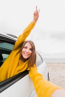 Reisende frau, die ein selfie im auto nimmt