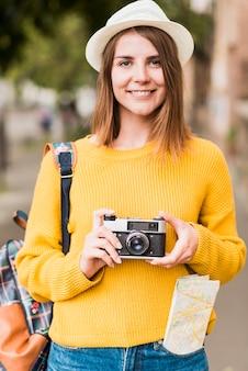 Reisende frau, die eine kamera hält