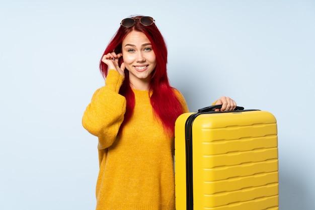 Reisende frau, die einen koffer lokalisiert auf blauer wand frustriert hält und ohren bedeckt