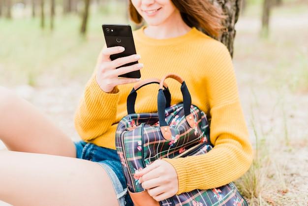 Reisende frau, die ihr telefon überprüft