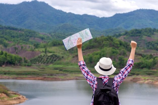 Reisende frau, die ihre hände mit karte aufsteigt und auf berg und see schaut