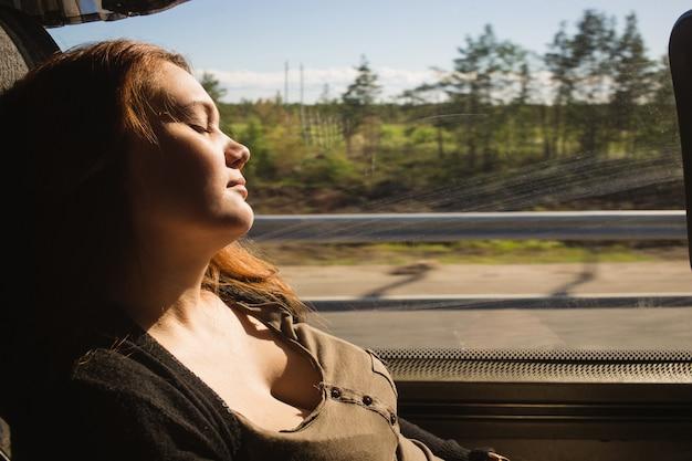 Reisende frau, die in einer zugreise neben dem fenster schläft