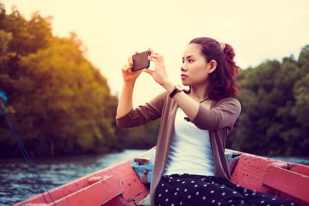 Reisende frau, die intelligentes telefon für das nehmen der fotografie auf dem boot bei sonnenaufgang verwendet