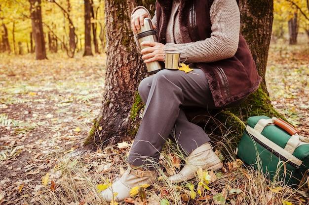 Reisende frau, die sich ausruht und tee im herbstwald trinkt