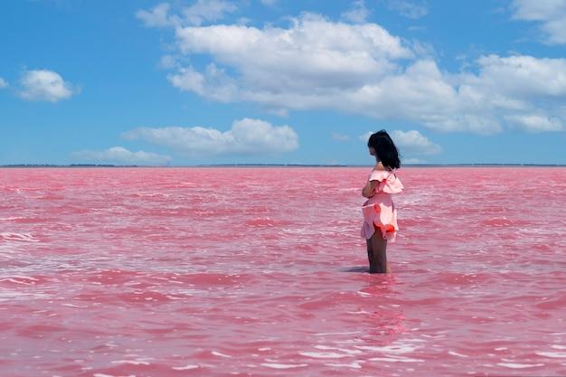 Reisende frau im rosa kleid betrachtet erstaunlichen exotischen rosa salzsee und blauen himmel. reisekonzept fernweh, platz für text kopieren.