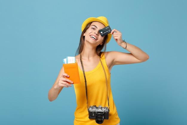Reisende frau in gelber kleidung hut hält karten kreditkartenkamera auf blau
