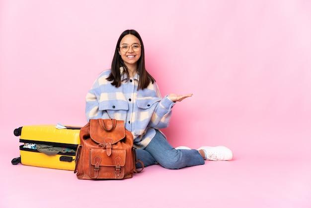Reisende frau mit einem koffer, der auf dem boden sitzt und den imaginären copyspace auf der handfläche hält, um eine anzeige einzufügen