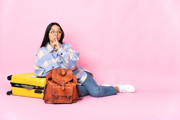 Reisende frau mit einem koffer, der auf dem boden sitzt und ein zeichen der schweigegeste zeigt, die finger in mund setzt