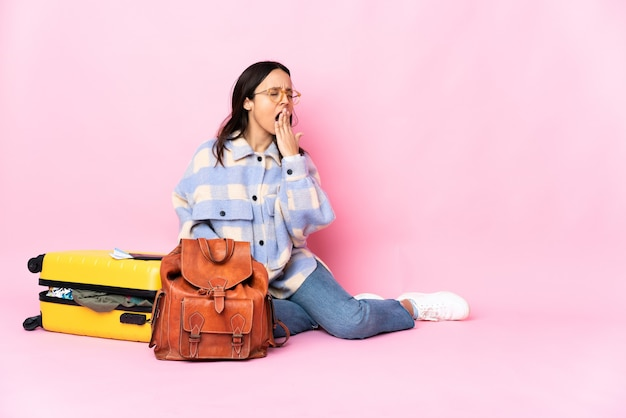 Reisende frau mit einem koffer sitzend auf dem boden gähnend