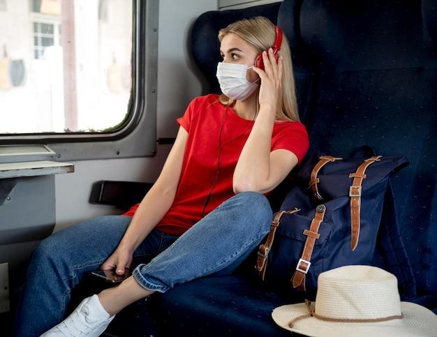 Reisende frau mit maske, die musik hört