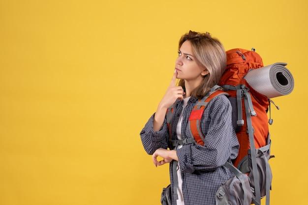 Reisende frau mit rotem rucksack, die über ihre reise nachdenkt
