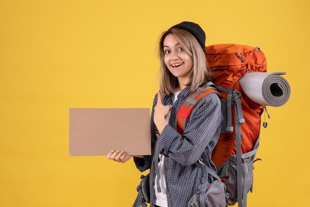 Reisende frau mit rotem rucksack mit karton nach hinten zeigend