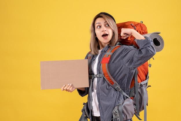 Reisende frau mit rotem rucksack mit pappe, die armmuskeln zeigt