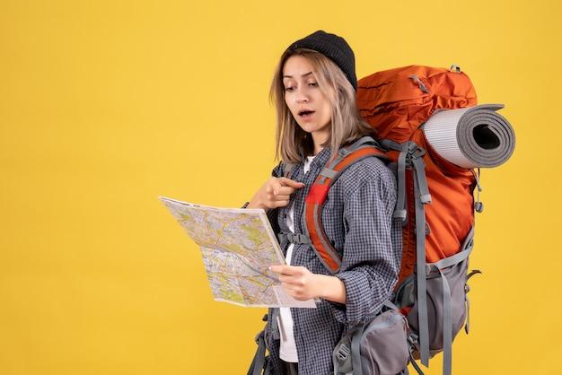 Reisende frau mit rucksack, die auf den ort auf der karte zeigt