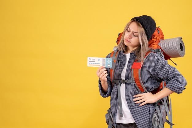 Reisende frau mit rucksack, die hand auf die taille legt und auf das ticket schaut