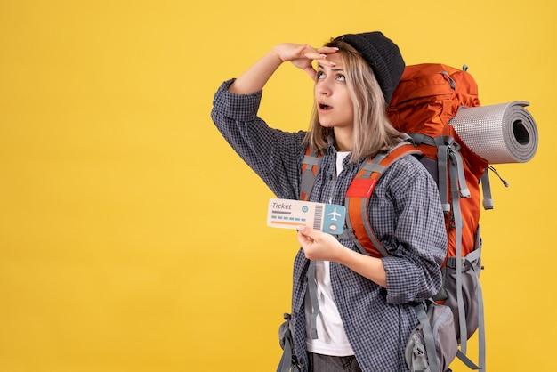 Reisende frau mit rucksack hält ticket nach oben