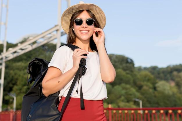 Reisende frau mit rucksack mit ihren ohrstöpseln