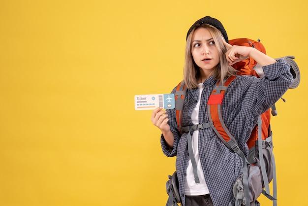 Reisende frau mit rucksack mit ticket, die über etwas nachdenkt