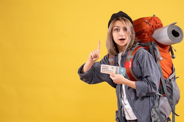 Reisende frau mit rucksack mit ticket zur decke zeigend