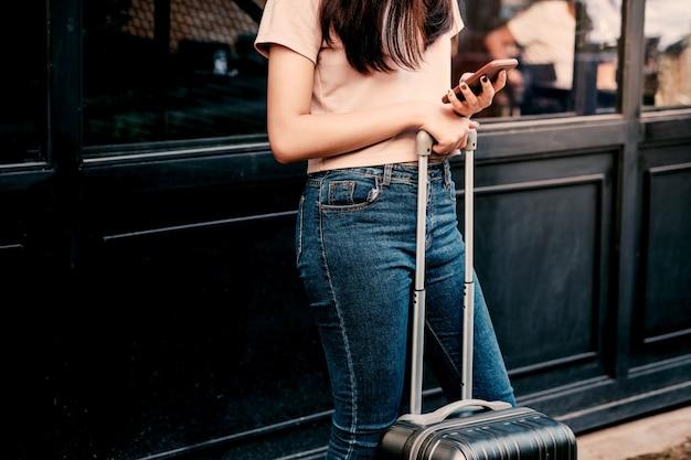 Reisende frauenhände unter verwendung des smartphones, das telefonkarte betrachtet.
