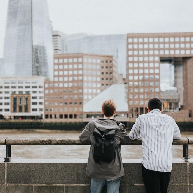 Reisende freunde bewundern die skyline von london von einer brücke aus