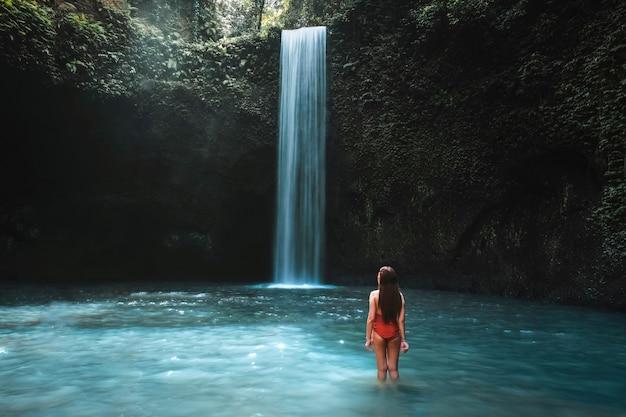 Reisende junge frau mit tropischem regenwald in bali das leben am schönen tibumana-wasserfall genießend.