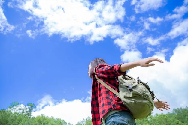 Reisende, junge frauen, schauen auf die atemberaubenden berge und wälder, reiselust-ideen, raum für botschaften, großartige momente der atmosphäre.