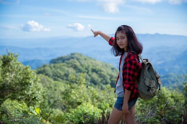 Reisende, junge frauen, schauen sich die erstaunlichen berge und wälder an, lassen sich von reiselust inspirieren,