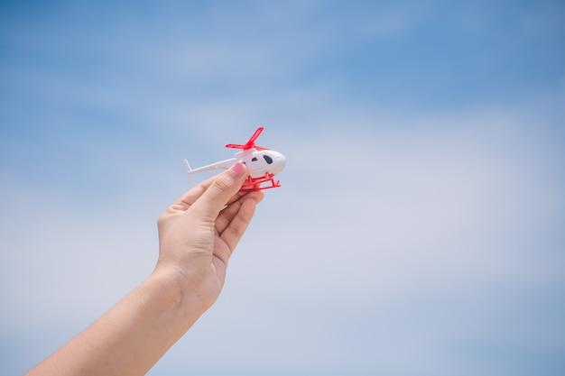 Reisende menschen konzept. hand zeigt den hubschrauber am himmel