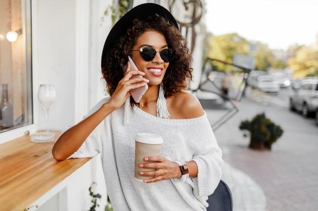 Reisende mischrassenfrau im stilvollen lässigen outfit, das draußen im stadtcafé entspannt, kaffee trinkt und per handy plaudert. trägt trendige accessoires und sonnenbrillen.