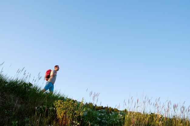 Reisende mit orangefarbenem rucksack gehen die hügel auf blauem himmelhintergrund hinunter