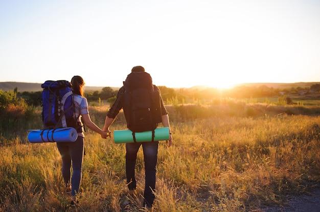 Reisende mit rucksack gehend in sonnenuntergang, hintere ansicht.