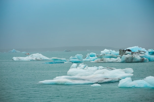 Reisende nehmen ein boot, um das schwimmende eis in den eisbergen des ozeans in der jokulsarlon-gletscherlagune in island zu sehen