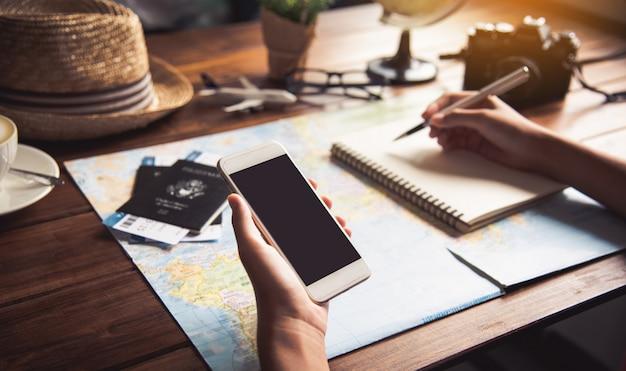 Reisende planen eine reise, indem sie die route auf der karte suchen und im internet nach informationen suchen.