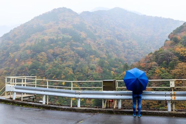 Reisende touristen, die einen blauen regenschirm halten, schauen auf die berglandschaft und den nebel im herbstlaub und die regenzeit in japan