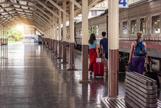 Reisende touristen gehen und schleppen gepäck, um den zug am bahnhof zu nehmen