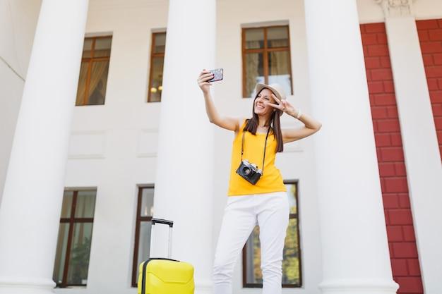 Reisende touristenfrau macht selfie-aufnahmen, die mit dem handy sprechen, einen freund anrufen, ein taxi buchen, ein hotel auf dem handy im freien. mädchen, das am wochenende ins ausland reist. tourismus reise lebensstil.