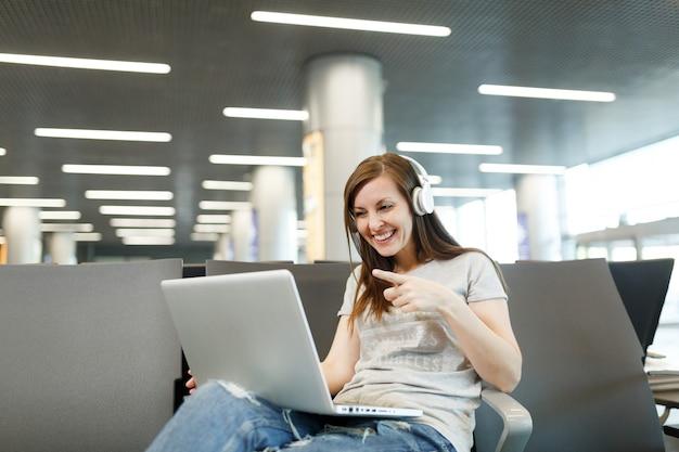 Reisende touristenfrau mit kopfhörern, die am laptop arbeiten und während des videoanrufs mit dem zeigefinger auf die webkamera zeigen, warten in der lobbyhalle am flughafen