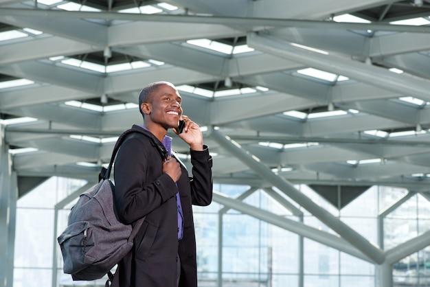 Reisender afrikanischer geschäftsmann, der mit handy und tasche geht