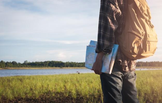 Reisender asiatischer junger männlicher tourist, der karte mit weinleserucksack an der seelandschaftsnatur holoding ist