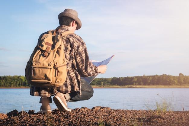 Reisender asiatischer junger männlicher tourist, der unter verwendung der lokalen karte mit weinleserucksack an der seelandschaftsnatur hockt